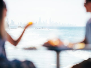 Currumbin couple man and woman sharing meal beachside cafe Surfers Paradise skyline
